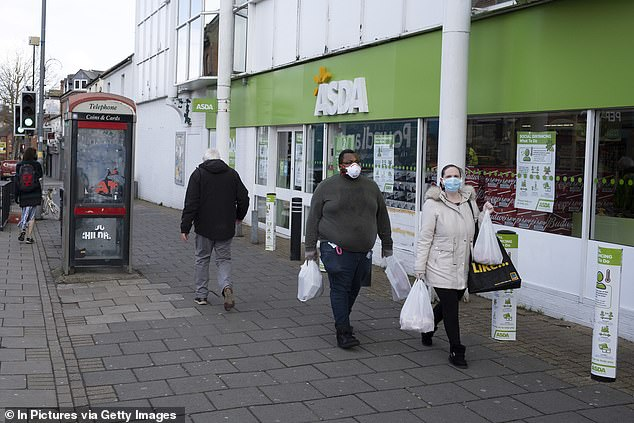 People wearing face masks are pictured carrying their shopping bags outside an Asda supermarket in April last year in Birmingham