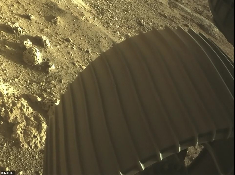 After landing, two of the Hazard Cameras (Hazcams) captured views from the front and rear of the rover, showing one of its wheels in the Martian dirt