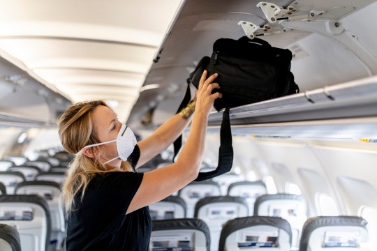 A woman wearing a mask puts her hand luggage into the airplane compartment