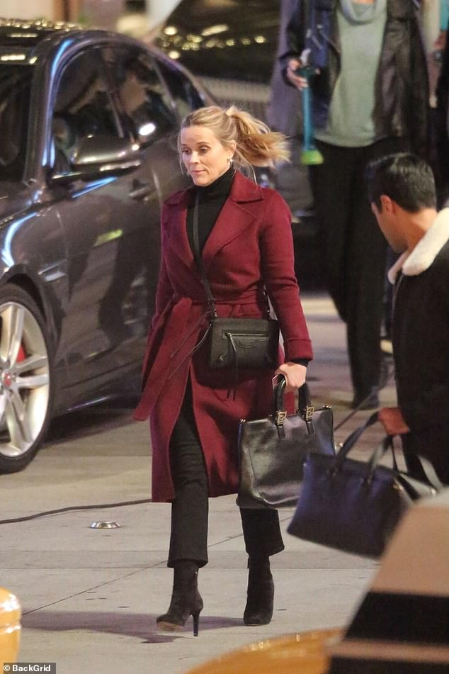 Splash of color: Reese was spotted elsewhere on set wearing a burgundy overcoat with wide lapels, as well as a black sweater and matching slacks