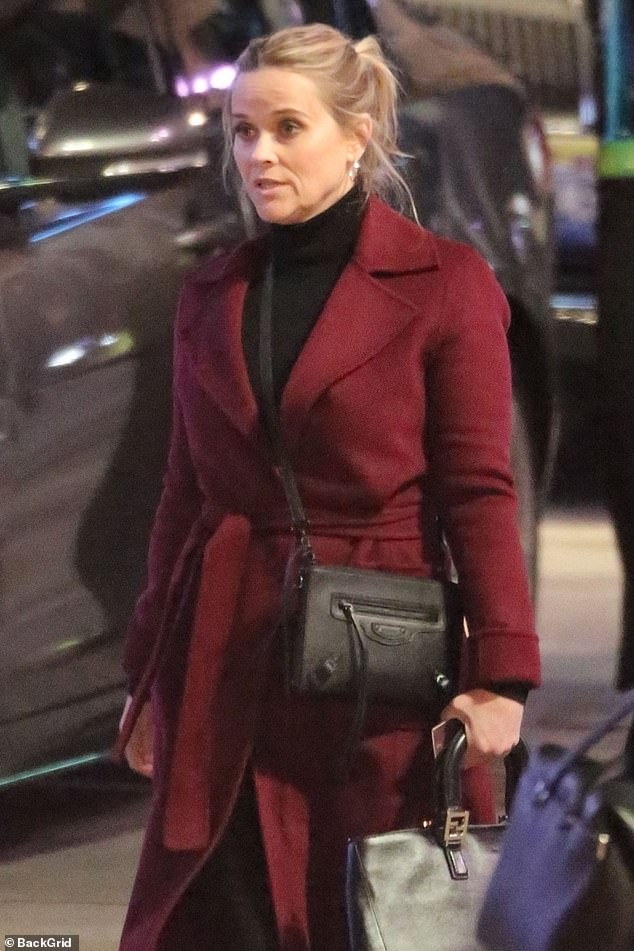 On the go: Like Aniston, she wore black suede boots, and she also had a black handbag slung across her shoulders while she carried a larger black bag in one hand
