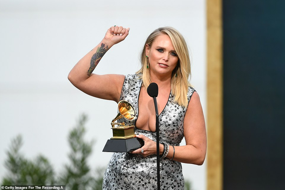 The 37-year-old singer thanked her fellow nominees - who happened to be all female as she said: ' We are such a family in country music so I feel like like I'm holding it for all of us, especially us girls'
