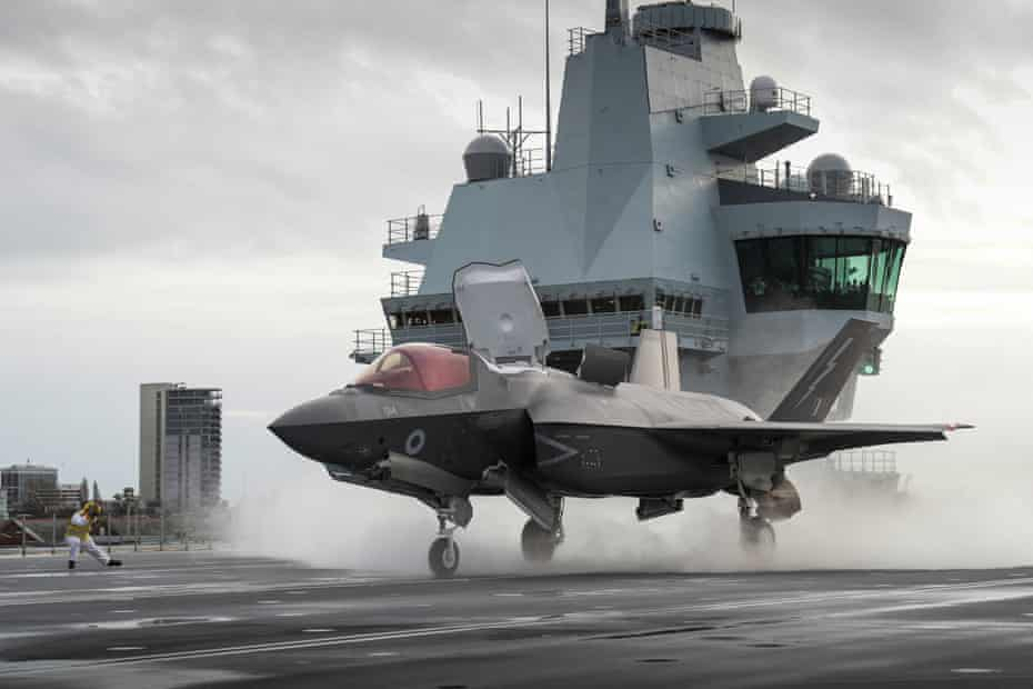 An RAF F-35B lightning jet preparing to take off from the flight deck of the HMS Queen Elizabeth at Portsmouth naval base.