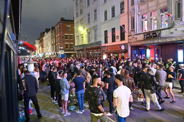 Revellers crowd the street outside bars in the Soho area of London on July 4