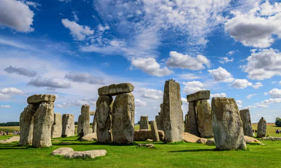Stonehenge, against a bright blue sky with light clouds