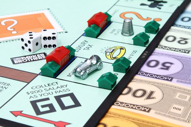 A partial view of a Monopoly game board showing the Go start square with various game playing pieces set up on the board.