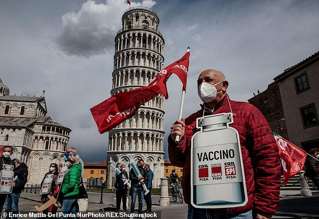 A retired man standing with a cardboard sign of the shape of a Covid vaccine in front of the leaning tower in Pisa, Italy, on March 18