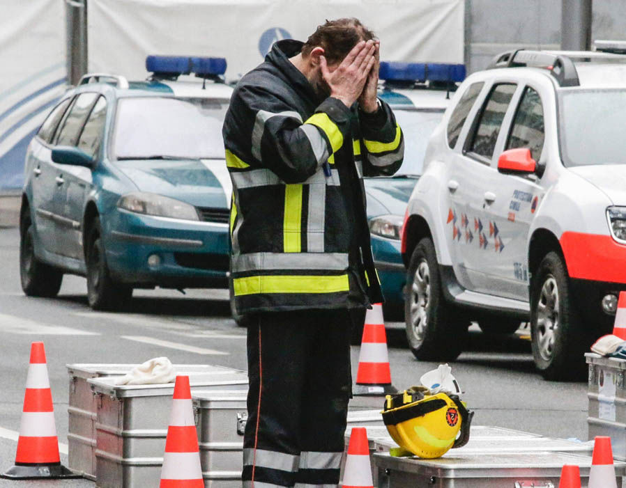 A member of the civil protection holds his face in his hands as he come back from the Maalbeek metro station in Brussels