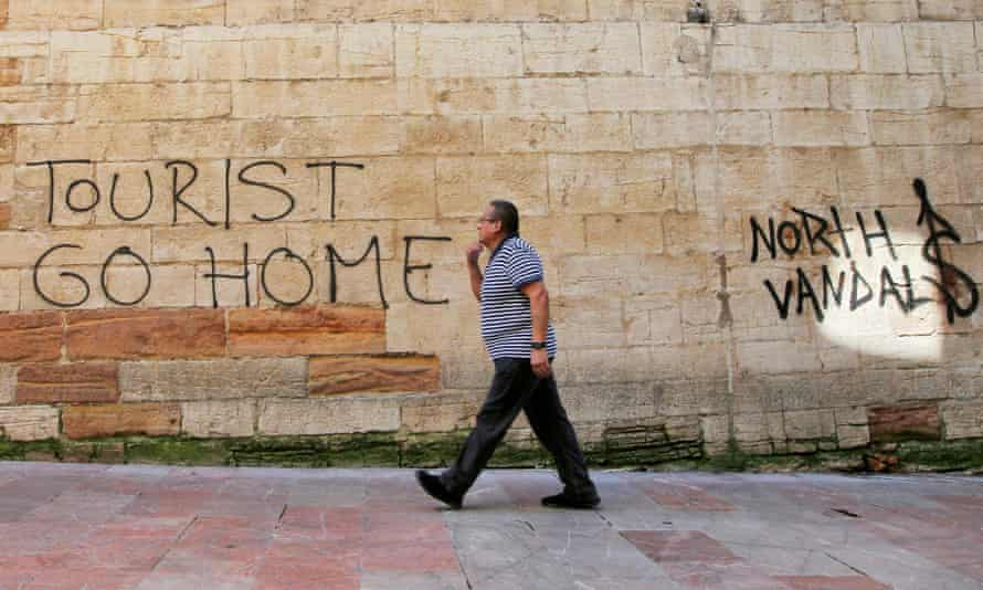 A man walks past a 'Tourists Go Home' graffitti on a wall close to the City Hall in Oviedo, northern Spain.