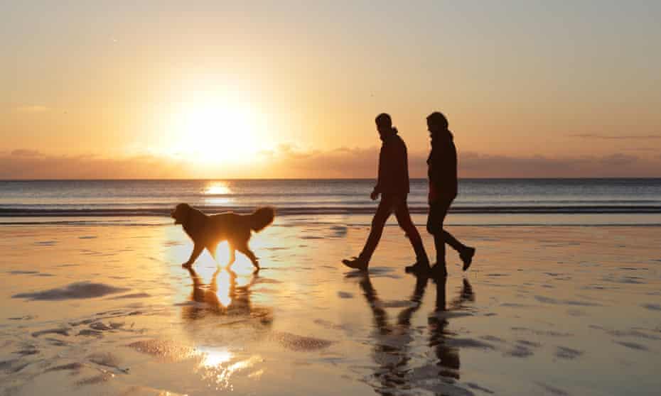 Couple walking do on beach at sunset