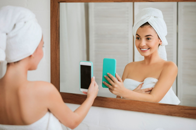 beautiful happy woman in towel taking selfie in front of mirror in the bathroom