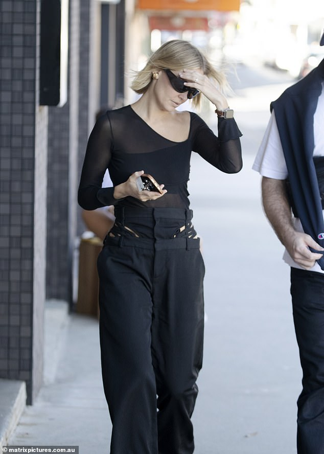 Accessories:She teamed the stylish shirt with designer pants, a pair of black boots and wore dark sunglasses