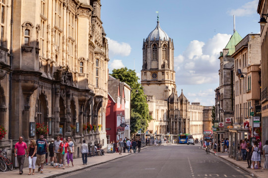 A busy street in Oxford. Christ Church cathedral can be seen rising above the rooftops.