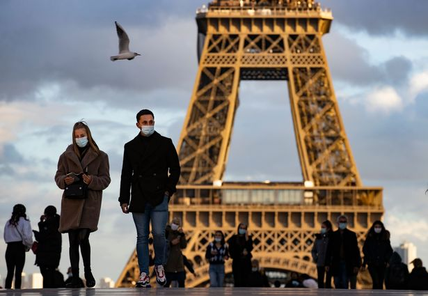 People wearing protective face masks walk near the Eiffel Tower