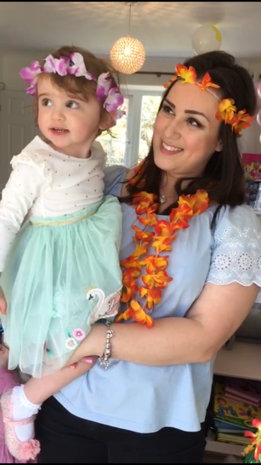 A woman holds her toddler daughter, both wearing flower crowns