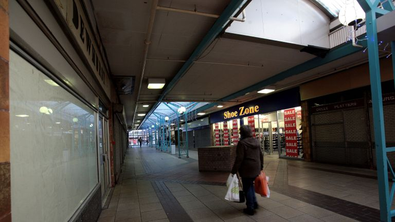 A woman walks past Shoe Zone, one of the only remaining shops open in the northern end of the Southside Shopping centre in Wandsworth, London, where retail units are closed awaiting redevelopment.