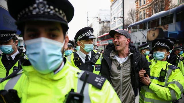 Police officers detain a demonstrator during a protest against the lockdown in London