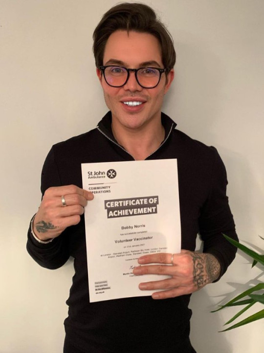 Bobby Norris holding certificate after completing volunteer vaccinator training