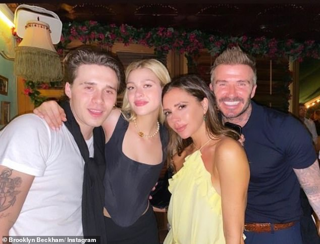 Family: Brooklyn later uploaded a throwback snap of himself and his beloved cosying up his parents David and Victoria during a fun night out