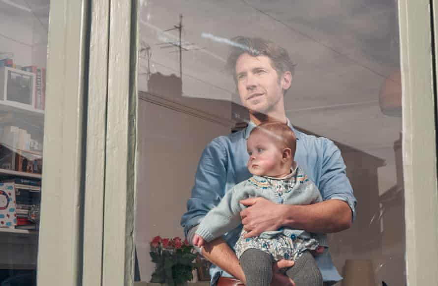Richard Godwin and his baby, Aubrey, seen though the window of their home
