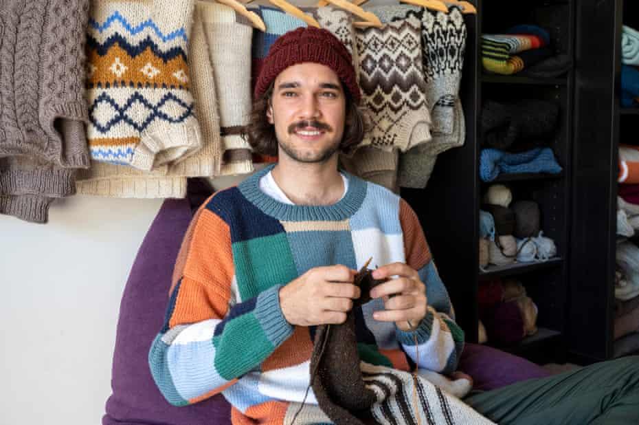 Australian knitter Brendan Girak, knitting, with jumpers hanging behind him. March 2021