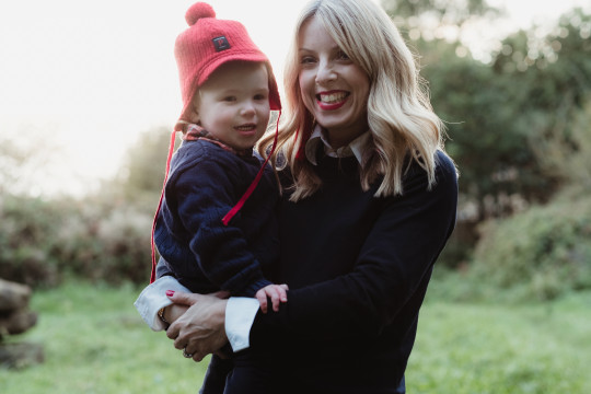 Rachel holding her youngest son as a toddler during a walk in the park
