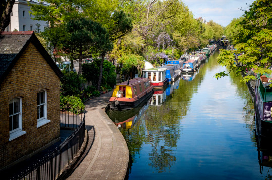 Rows of houseboats and narrow boats on the canal banks at Regent's Canal next to Paddington in Little Venice, London - England, UK
