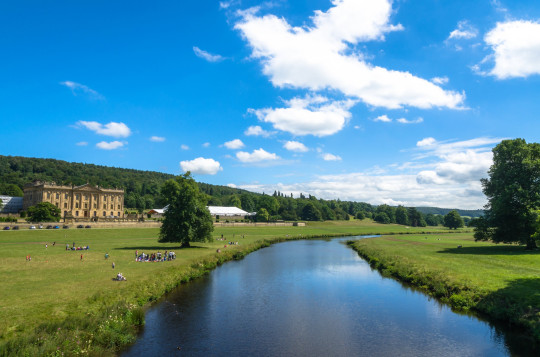 BAKEWELL, DERBYSHIRE, ENGLAND - JULY 16, 2017: Tourists picnic at the magnificent Chatsworth House by River Derwent in the romantic Derbyshire Dales. The house is the seat of the Duke of Devonshire.; Shutterstock ID 683514937; Purchase Order: -