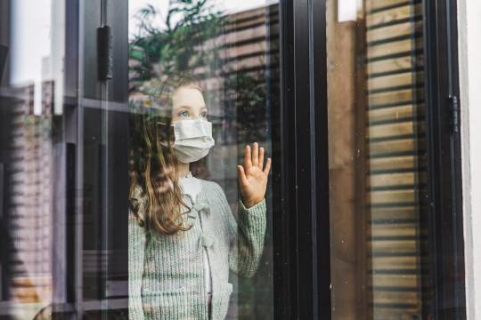 Young girl looking through window with mask