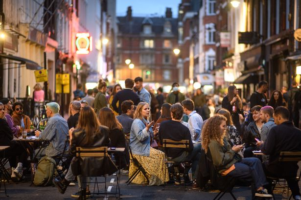 People eat and drink oudoors in Soho, London, as coronavirus lockdown restrictions are eased across England