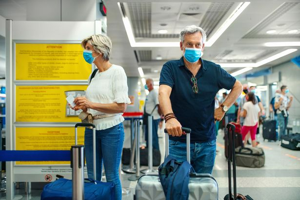 Closeup front view of a mid 50's couple waiting for a flight after coronavirus travel ban has been lifted.