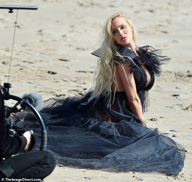 Windswept:In another shot the home-selling hotshot knelt down in the sand to shoot a shouldering stare over her shoulder while her hair was whipped up by the wind