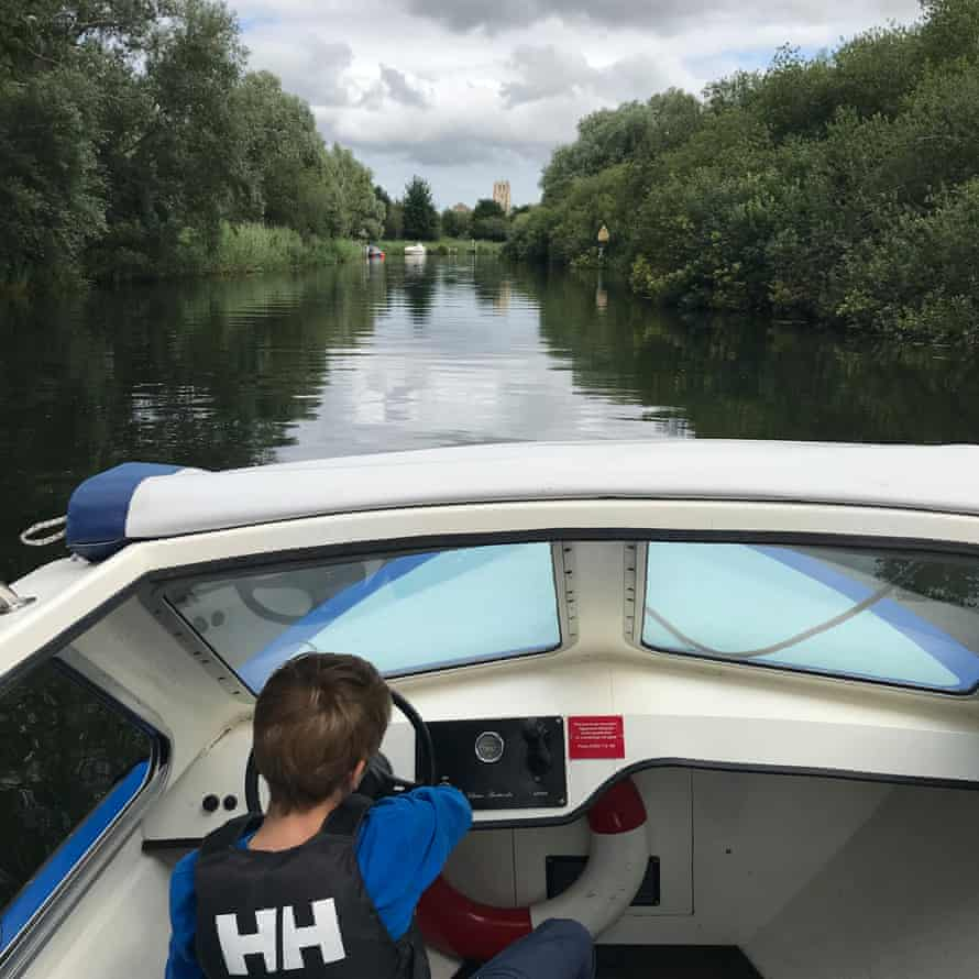 The writer's son pilots their electric boat along the river, Suffolk, UK.