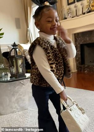 Work it: The two-year-old sweetly held up her new white Dior quilted handbag, which cost $4,212, and UGG boots