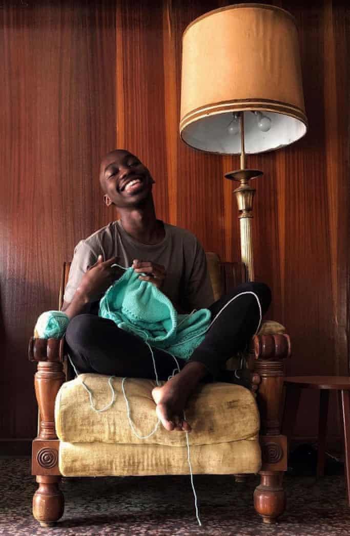 Ola Ogunlolu sitting on a chair, knitting