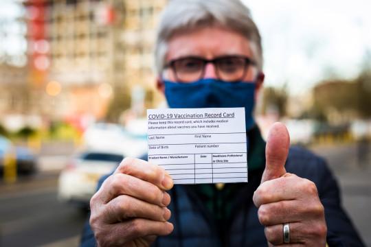 Senior man holding Covid-19 vaccination record card