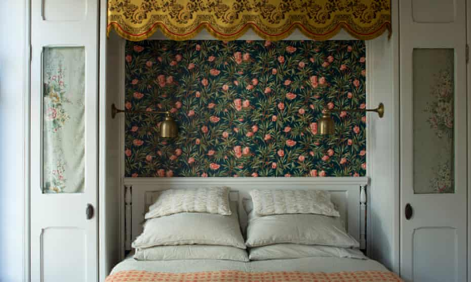 Bedroom with decorative wallpaper behind the bed