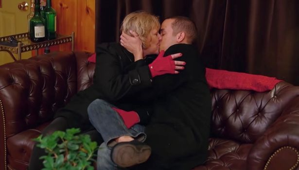 Kyle kissing an older woman on a sofa