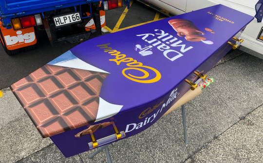 This photo provided by Ross Hall, shows a chocolate bar designed casket in Auckland, New Zealand on April 30, 2020. Auckland company Dying Art makes unique custom caskets which reflect the people who will eventually lay inside them, whether it's a love for fire engines, a cream doughnut or Lego. (Ross Hall via AP)