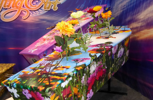 This photo provided by Ross Hall, shows floral designed caskets in Auckland, New Zealand March 17, 2016. Auckland company Dying Art makes unique custom caskets which reflect the people who will eventually lay inside them, whether it's a love for fire engines, a cream doughnut or Lego. (Ross Hall via AP)