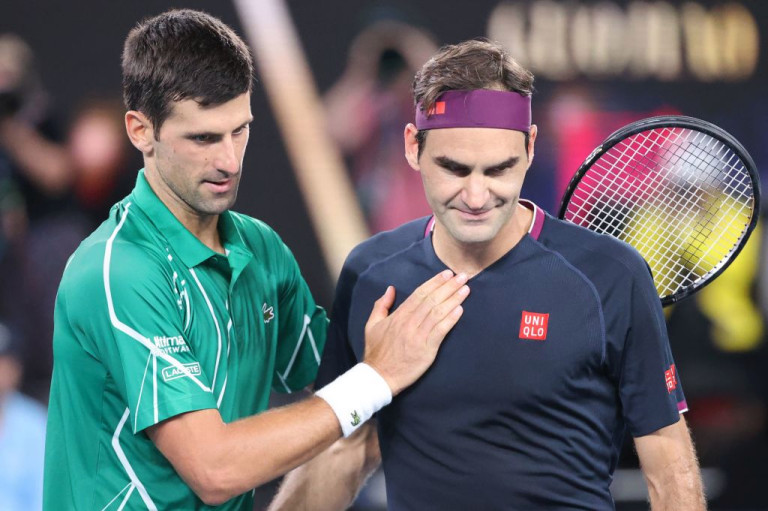 Serbia's Novak Djokovic (L) pats Switzerland's Roger Federer after his victory during their men's singles semi-final match on day eleven of the Australian Open tennis tournament in Melbourne on January 30, 2020.