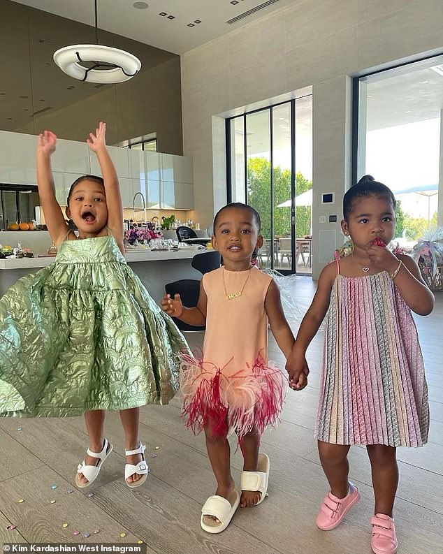 Stylish tots: The cute snaps shows Stormi in a pastel green lamé dress, Chi in a peach dress with feather trim and True in a striped multicolor sundress