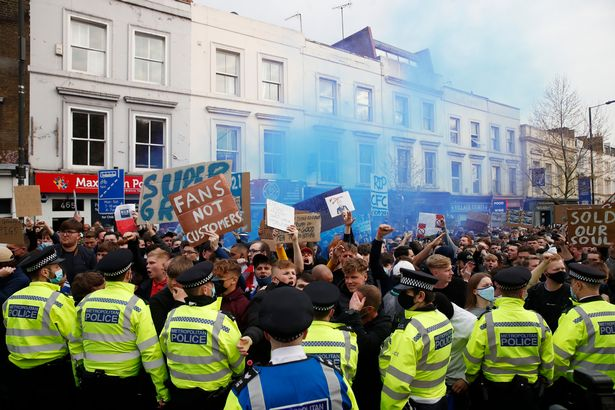Soccer Football - Premier League - Chelsea v Brighton & Hove Albion - Stamford Bridge, London, Britain - April 20, 2021 Police officers are seen as Chelsea fans protest the planned European Super League outside the stadium before the match.