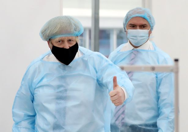 Britain's Prime Minister Boris Johnson, wearing a face mask and a hair net, visits the Northumbria Healthcare NHS Trust personal protective equipment (PPE) manufacturing hub in Seaton Delaval, northeast England, on February 13, 2021 during a one-day visit to the region to visit manufacturing facilities and see the ongoing COVID-19 response
