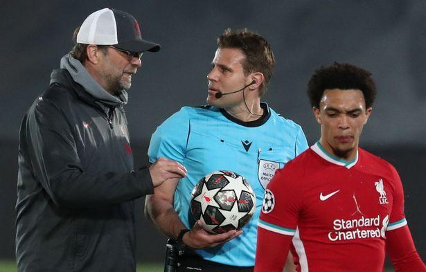 Liverpool's head coach Jurgen Klopp (L) talks with referee Felix Brych
