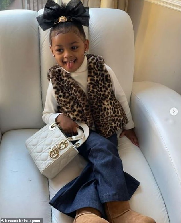 Sweet: Cardi B's two-year-old daughter Kulture posed with her new Dior handbag and Chanel earrings in a collection of sweet snaps shared to Instagram on Wednesday