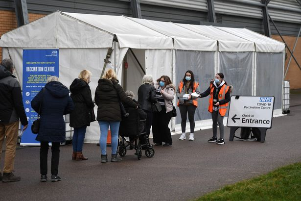 Members of the public wait in a queue to receive a dose of a Covid-19 vaccine in Colchester