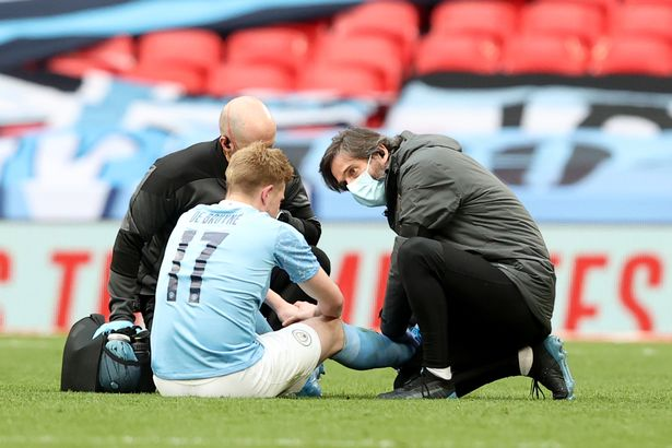 An injured Kevin de Bruyne of Manchester City is tended to during the Semi Final of the Emirates FA Cup match between Manchester City and Chelsea FC at Wembley Stadium on April 17, 2021 in London, England.