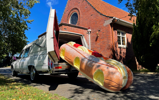 This photo provided by Ross Hall, shows a cream doughnut shaped coffin for the funeral of Phil McLean outside a church in Tauranga, New Zealand on Feb 17, 2021. Auckland company Dying Art makes unique custom caskets which reflect the people who will eventually lay inside them, whether it's a love for fire engines, a cream doughnut or Lego. (Ross Hall via AP)
