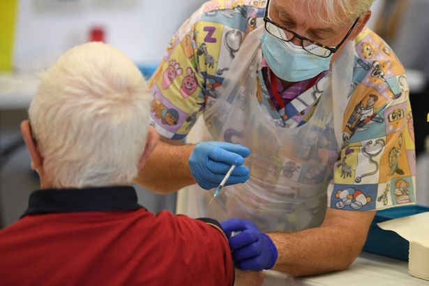 A health worker administers a dose of the BioNTech/Pfizer covid-19 vaccine at a vaccination clinic set up inside the Derby Arena at Pride Park in Derby, Derbyshire on March 31, 2021